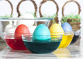 Coloring easter eggs four in glass bowls of dye one red one turquoise one yellow and one blue white in large glass bowl and Royalty Free Stock Images