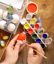 Coloring easter eggs paint and brushes hand in the shot Royalty Free Stock Photos