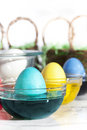 Coloring easter eggs three in glass bowls of dye one turquoise one yellow and one blue white in large glass bowl and baskets Stock Photography