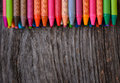Coloring pencils aligned on wooden background Royalty Free Stock Photos