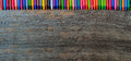 Coloring pencils aligned on wooden background Royalty Free Stock Image