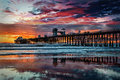 Colors of the oceanside pier sunset in is nearly silhouetted with lights just coming on as sun has dropped below pacific ocean Royalty Free Stock Photography