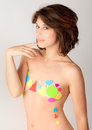 Colors and shapes an image of a pretty young woman with her top covered by bright foam stickers Royalty Free Stock Image