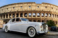 Colosseum white rolls royce car in front of the s construction started in ad under the emperor vespasian and was Royalty Free Stock Image