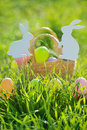 Coloured Easter Eggs In Basket Padded Out With Rabbit Decorations Royalty Free Stock Photo