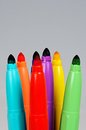 Coloured felt tipped pens against a grey background Stock Images