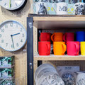 stock image of  Coloured mugs and wall clocks on sale in a shop.