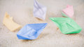 Coloured Paper Ships Chaotic Laying on Sandy in the Desert Royalty Free Stock Photo