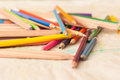 Coloured pencils scattered on table crayons a Royalty Free Stock Image