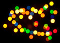 Coloured specks of light on a black background Royalty Free Stock Images