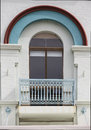 Colourful arched window in colonial era building with iron lace balcony railing Royalty Free Stock Images