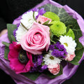 Colourful bouquet of mixed flowers overhead view a arranged in purple tissue paper to be carried as an accessory at a wedding Stock Photos