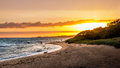 Colourful coastline sunset with beautiful beach and ocean Royalty Free Stock Photo