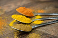 Colourful Curry Spices in Silver Spoons on Dark Wood Royalty Free Stock Photo