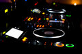 Colourful dj deck and turntables illuminated at night at a discotheque concert or party with a close up view of the equipment for Royalty Free Stock Images