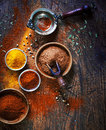 Colourful dried ground spices overhead view of in bowls spilling onto an old aged scored wooden surface in a country kitchen with Stock Image