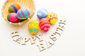 Colourful easter egg in basket with wooden text Stock Images