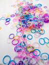 Colourful elastic bands loom against a white table top Royalty Free Stock Photo