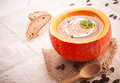 Colourful fall pumpkin soup served in the hollowed out gourd on a piece of rustic burlap with a wooden spoon Royalty Free Stock Photos