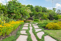 Colourful flowerbeds and winding grass pathway in an attractive thailand formal garden Royalty Free Stock Photos