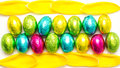 Colourful foil wrapped easter eggs framed yellow tulip petals Stock Photos