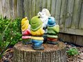 Colourful Garden Gnomes Standing on a Tree Stump Royalty Free Stock Photo