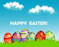 Colourful happy easter greeting card design with a row of decorated eggs in fresh green spring grass under a blue sky with Stock Photo