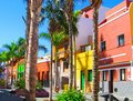Colourful houses and palm trees on street in Puerto de la Cruz town, Tenerife, Canary Islands, Spain. view of volcano Teide Royalty Free Stock Photo