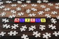 Colourful jigsaw puzzle and alphabet tiles with AUTISM word on wooden table Royalty Free Stock Photo
