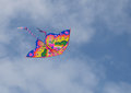 Colourful kite in the sky a butterfly shaped flying high against a fluffy cloud background blue Royalty Free Stock Photo