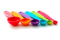 Colourful measuring spoons six plastic of different colours on an isolated white background Stock Images
