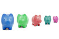 Colourful piggy banks in a row over white background Royalty Free Stock Photos