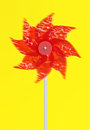 Colourful red pinwheel a childs toy with plastic vanes pinned to a stick that revolves in the wind like a windmill Stock Images