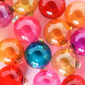 Colourful translucent glass Christmas baubles on pink background. Creative decoration. Royalty Free Stock Photo