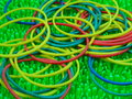 Colourfull rubber bands on artificial green grass background Stock Photography