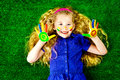 Colours bright laughing little girl painted in colors lying on green grass happy childhood Royalty Free Stock Photo