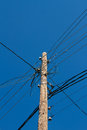 Column with electric wires against the blue sky Stock Image