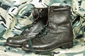 Combat boots old model high on camouflage background Stock Images