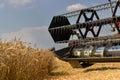 Combine harvester close up. Combine harvester harvesting wheat. Grain harvesting combine. Combine harvesting wheat. Wheat field bl Royalty Free Stock Photo