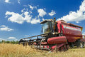 Combine harvester at the edge of grain field during harvest time Royalty Free Stock Photo