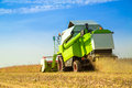 Combine harvester harvesting soybean at field. Royalty Free Stock Photo
