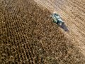 Combine harvester picking seed from fields, aerial view of a field with a combine harvester with cornhusker gathering the crop Royalty Free Stock Photo