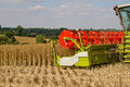 Combine harvester at rape harvest Royalty Free Stock Image