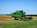 Combine harvesting crop corn grain fields. Royalty Free Stock Photo