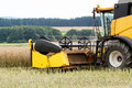 Combine harvesting rape yellow in summer on farmlad rural scene Stock Photography