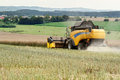 Combine harvesting rape yellow in summer on farmlad rural scene Stock Image