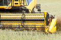 Combine harvesting rape yellow in summer on farmlad rural scene Stock Photos