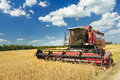 Combine machine with air-conditioned cab harvesting oats on farm field Royalty Free Stock Photo