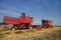 Combines parked in field in fertile plain Royalty Free Stock Photo