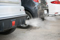 Combustion fumes coming out of car exhaust pipe Royalty Free Stock Photo